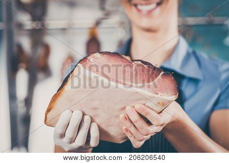 Young woman or female butcher with raw ham in butchers shop selling meat