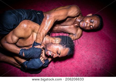Two African American opponents struggling for dominance in ground fighting during MMA match