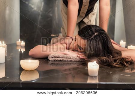 Young woman lying down while enjoying the acupressure techniques of traditional Thai massage at luxury spa and wellness center