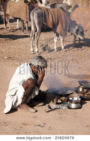 Nomad making a phone call while cooking his meal at Nagaur's cattle fair in Rajasthan.