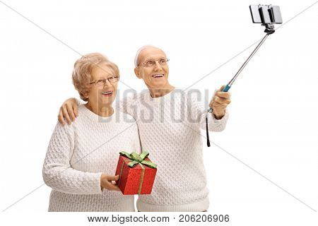 Elderly couple with a gift taking a selfie with a stick isolated on white background