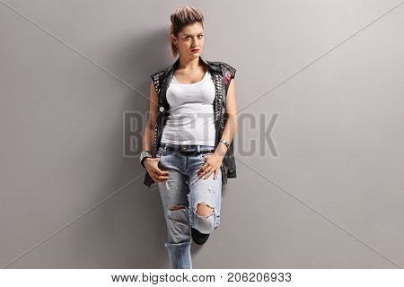 Angry punk girl leaning against a wall and looking at the camera