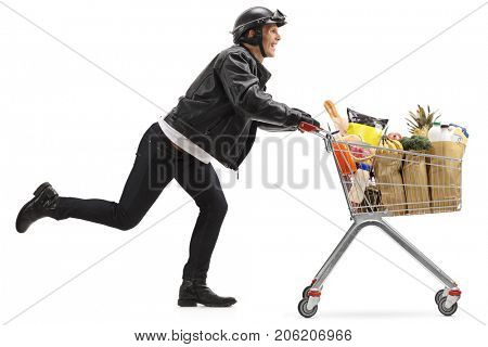 Full length profile shot of a biker pushing a shopping cart filled with groceries isolated on white background