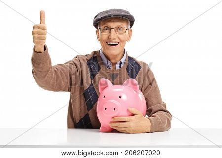 Cheerful senior with a piggybank seated at a table making a thumb up sign isolated on white background
