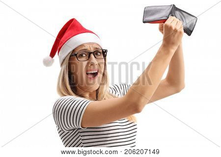 Disappointed woman with a santa hat holding an empty wallet and looking at the camera isolated on white background