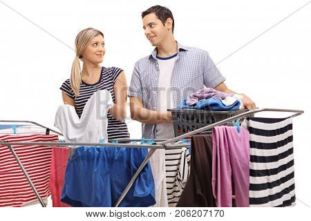 Young couple hanging clothes on a rack dryer together isolated on white background