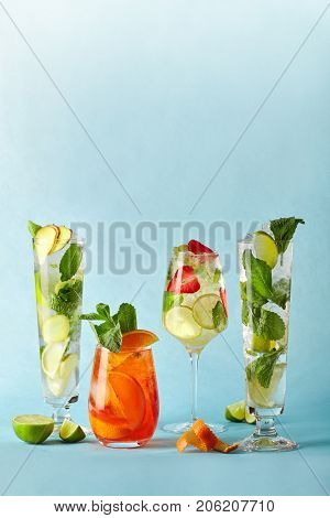 Mojito and aperol syringe with lime lemon ginger orange and strawberries in glass glasses