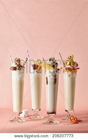 Milkshake with biscuits, chocolate, sweets and candy with straws in glass