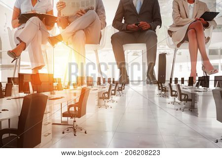 Open space with black computers against group of well dressed business people waiting