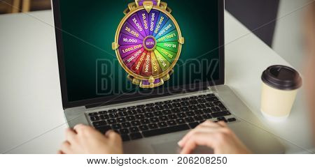 Graphic image of wheel of fortune on mobile screen against cropped hands of woman using laptop