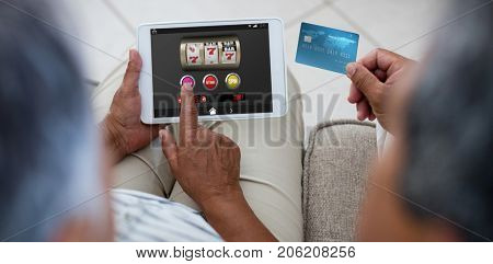 Slot machine with icons on mobile display against senior couple doing online shopping on digital tablet