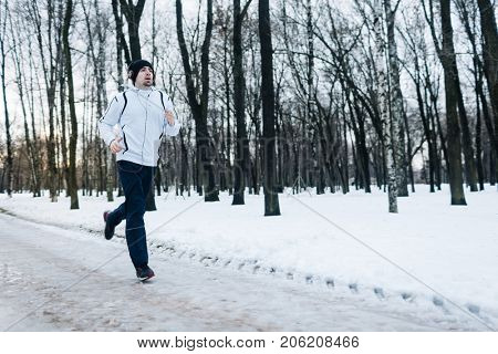 Active guy in sportswear running in wintery park in the morning