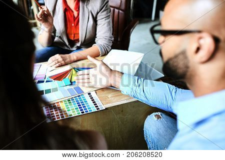 One of designers pointing at variety of colors in palette while consulting with colleagues