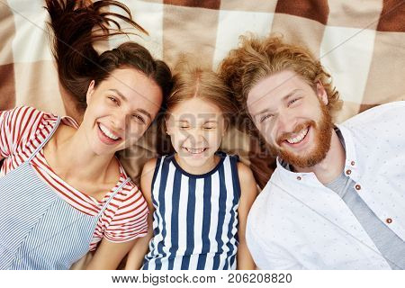 Carefree young man, woman and little girl looking at camera while relaxing on plaid