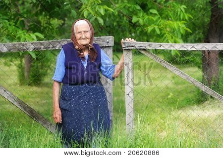 Old woman standing beside gate