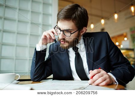 Smart man phoning about curious vacancy in newspaper while seeking for job