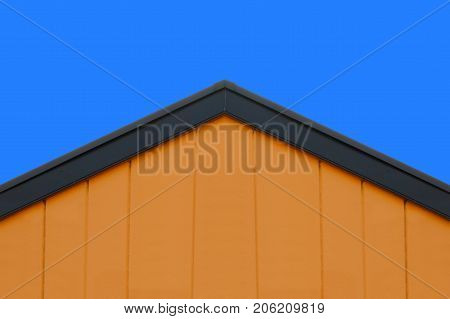 orange concrete wall gable roof house with blue sky