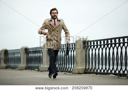 Stylish man with drink and briefcase hurrying for interview or appointment