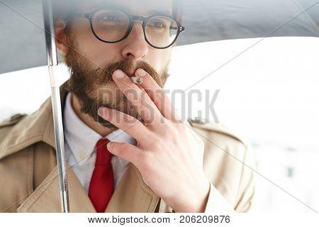 Elegant and posh man in red tie and beige trench smoking under umbrella