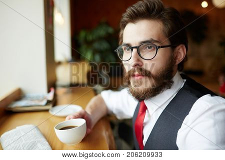 Bearded man in eyeglasses and elegant formalwear having five oclock tea