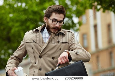 Hurrying businessman in elegant trench looking at watch in urban environment