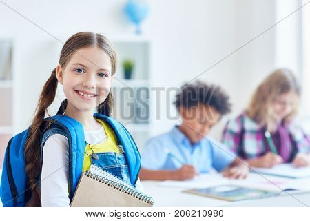 Smiling little scholar with rucksack and notepads on background of schoolboys