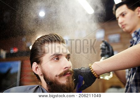 Hair master spraying hair-styling product on client hair