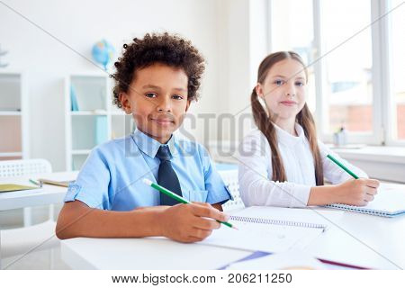 Adorable classmates with pencils drawing by desk at lesson