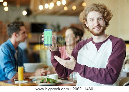 Handsome bearded man looking at camera with toothy smile while pointing at blank screen of smartphone, his best friends sitting behind him and talking to each other at cozy cafe