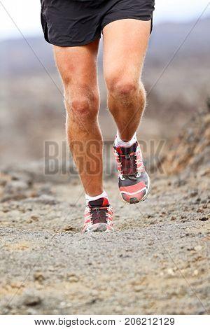 Sport athlete man running shoes trail desert run training cardio for marathon race. Legs of runner hiking or walking on path landscape.