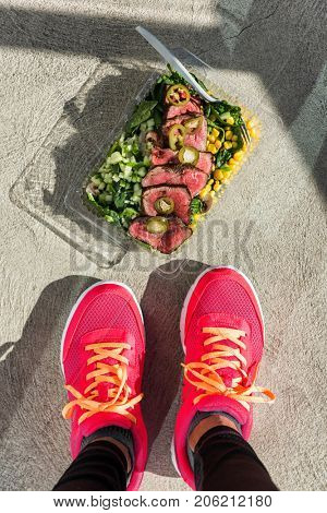 Gym foot paleo diet fitness woman taking top view picture of her ready-to-eat salad and steak lunch box delivery online service at gym or home for healthy food. Meal prep for bodybuilders lifestyle.