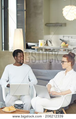 Intercultural young couple with laptops networking and consulting at home
