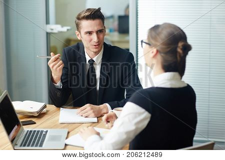 Group of young financial managers in formalwear gathered together at meeting room and preparing annual accounts, blurred background