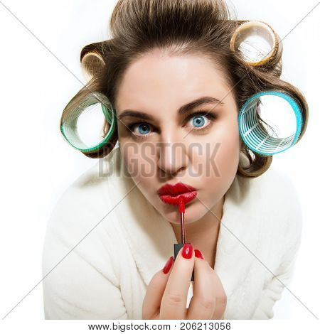 Funny portrait of blue-eyed woman dressing gown and in curlers lipstick in red her lips looking at camera like in the mirror over white background.