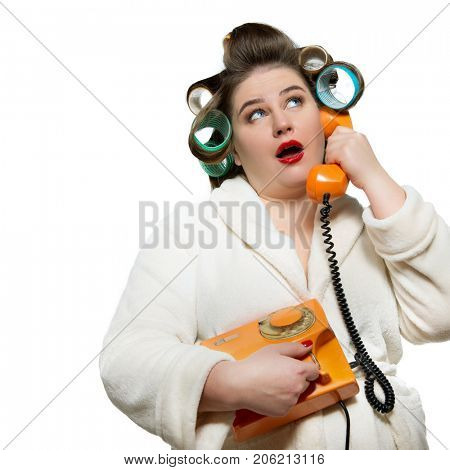 Funny portrait of woman in dressing gown and in curlers with red lips and manicure calling retro phone, over white background.