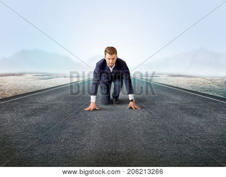 Young determined businessman kneeling before blank running track