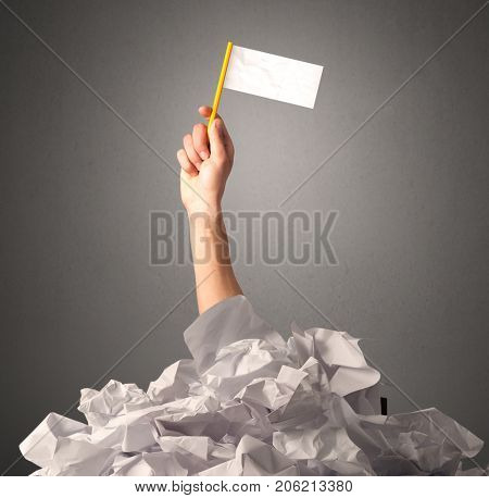 Female hand emerging from crumpled paper pile holding a white blank flag