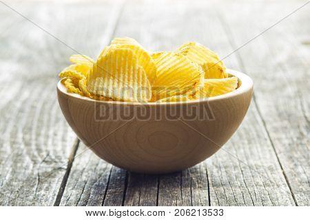 Crispy potato chips in wooden bowl. Salted potato chips.