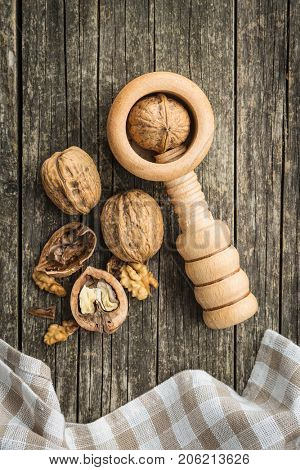 Cracked dried walnuts and nutcracker on old wooden table.