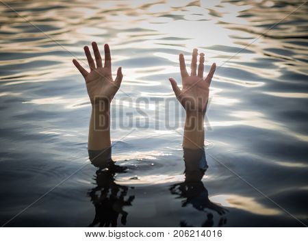 Drowning victims Hand of drowning woman needing help with selective focus. Failure and rescue concept.
