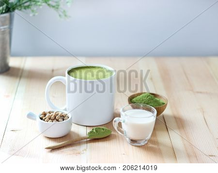 Closed Up Hot Green Tea Latte On Wooden Table With White Background. Decorrate With Powder Extract A