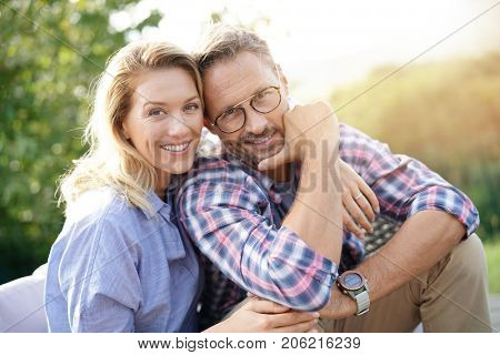 Portrait of mature couple relaxing in outdoor sofa