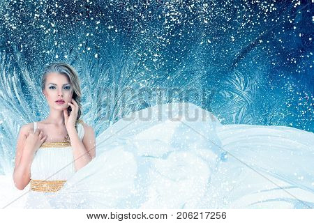 Winter fantasy fashion portrait of young attractive woman over snowy Christmas background