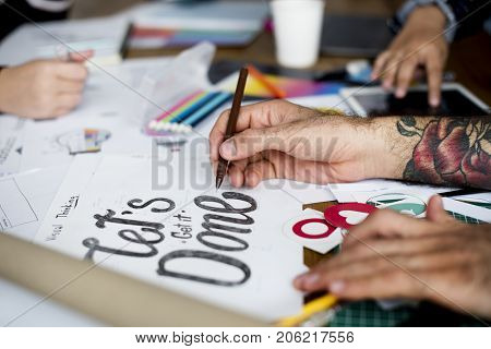 Hands Writing Let's Get It Done Phrase on Paper Art Design