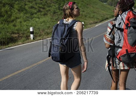 Diverse Backpacker Women Walking along The Street Side
