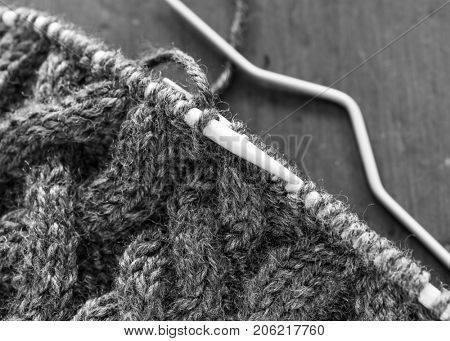 Homemade winter hat with intensive cable design in black and white.