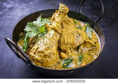 Traditional Indian curry chicken as close-up in a Korai