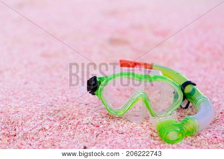 Snorkeling equipment mask and snorkel on beach made of small pink shells