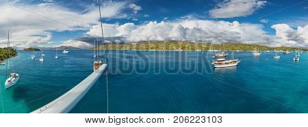 Panoramic view on beautiful Adriatic bay with yachts, shot from main spar of sailing boat.