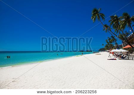 BORACAY, PHILIPHINES-MARCH 17, 2016: Tropical vacation on white sand beach with sun, blue sky and palm trees. White beach at Boracay island on March 17, 2016, Philiphines.
